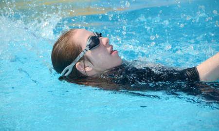 backstroke: Backstroke swimming - young woman  teenager swimming in the pool