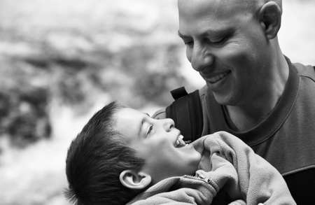 Father and Son - black and white portrait of a father and son laughing and loving; a father holding his son