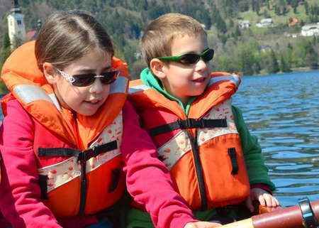Brother and sister on a boat - Two siblings waring lifevests on a sailing on rowboart on Bled Lake, Slovenia photo
