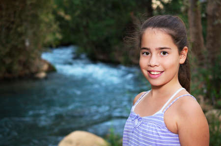 Beautiful teenage girl relaxing on the Jordan River photo