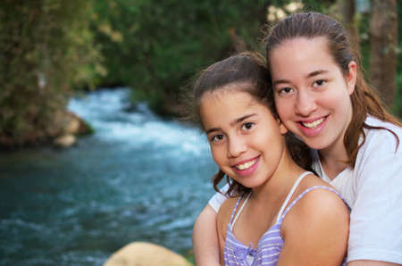 Beautiful teenage sisters relaxing on the Jordan River photo