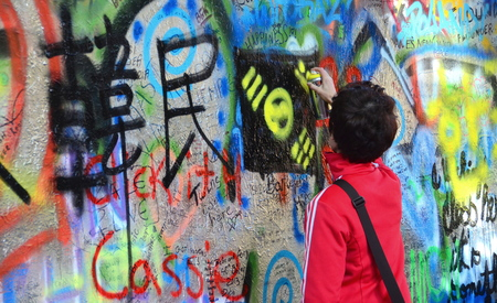 PRAGUE, CZECH REPUBLIC - OCT 13: Unidentified person adding grafitti to the John Lennon Wall on Oct. 13, 2013 in Prague, Czech Republic.  Since the 1980s, the wall has been filled with John Lennon-inspired graffiti and pieces of lyrics from Beatles songs.
