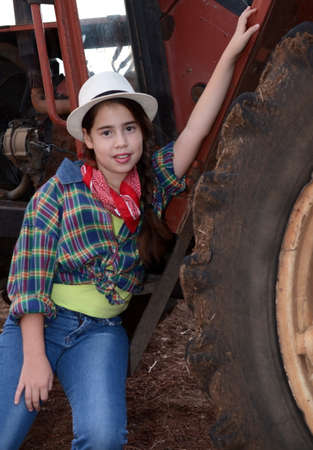 Girl in western clothes  cowgirl  on a tractor photo