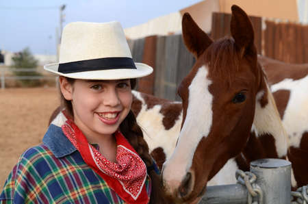 Girl in western clothes  cowgirl  with a horse photo