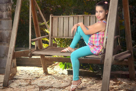Beautiful teenage girl on a swinging seat photo