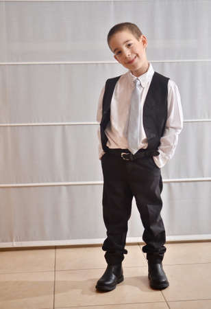 Six year old boy dressed up in a vest and tie photo