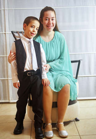 Young woman all dressed up in a teal dress for her Sweet Sixteen party with her brother in a vest and tie photo