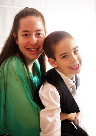 sweet sixteen: Young woman all dressed up in a teal dress for her Sweet Sixteen party with her brother in a vest and tie
