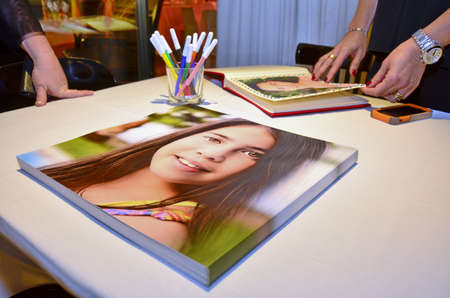 mitzvah: People looking at a fancy Bat Mitzvah Photobook