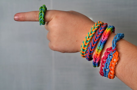 Little boy wearing colorful loom band rubber bracelets and ring Stock Photo