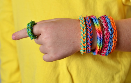 loom: Little boy wearing colorful loom band rubber bracelets and ring Stock Photo