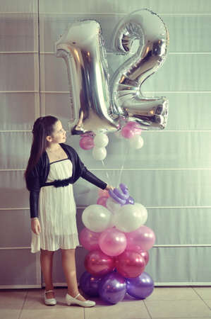 Secular 12-year-old Israeli teenager celebrating her Bat Mitzvah with special balloons Girl Scout  vintage-processed  photo