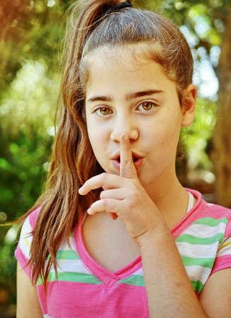 shushing: Portrait of a young Israeli girl - shushing, shhh, quiet Stock Photo