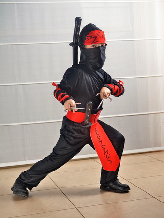 An Israeli 6-year-old boy dressed up for Purim as a NinjaSamurai demonstrating fight moves with his sword Stock Photo