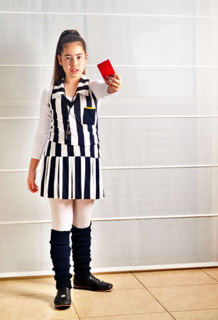An Israeli 12--year-old teenager girl dressed up for Purim as soccer (football) referee using her whistle and pulling out a red card photo