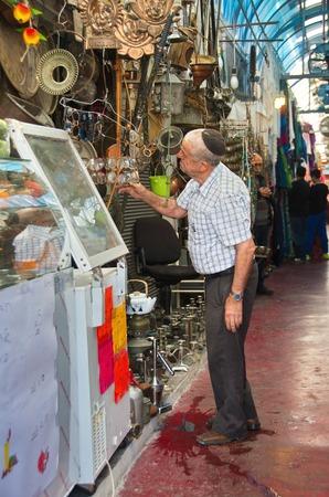 yaffo: Jaffa, Israel - 11 de abril 2014: Un se�or examinar merchendize ancianos en la ciudad vieja �rabe de Jaffa Mercado en la ma�ana del viernes Editorial