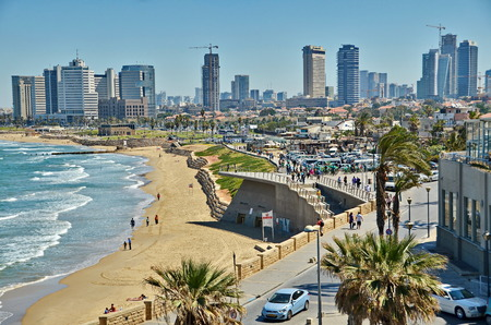 tel: TEL AVIV, ISRAEL - APR 11, 2014:People on the Mediterranean  beach and Tel Aviv, Israel boradwalk with the city sky line and towers in the background Editorial