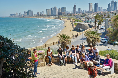 TEL AVIV, ISRAEL - APR 11, 2014: A group of turists near the Mediterranean  beach and Tel Aviv, Israel boradwalk with the city sky line and towers in the background