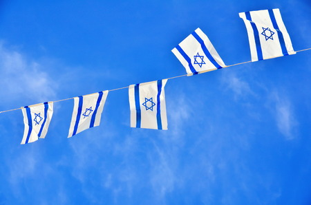 Israel flags in a chain in white and blue showing the Star of David hanging proudly for Israels Independence Day (Yom Haatzmaut) photo