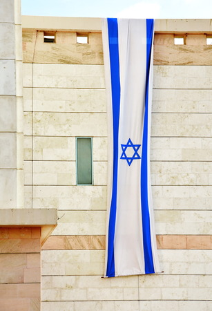 Israel flag in white and blue showing the Star of David hanging vertically on a modern building for Israels Independence Day (Yom Haatzmaut) photo
