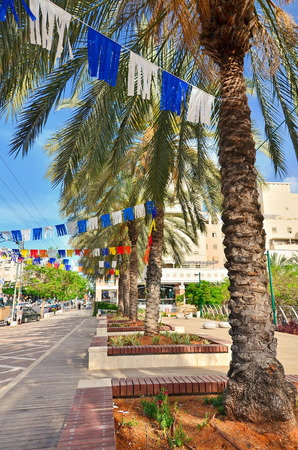 KFAR SABA, ISRAEL - APR 25, 2014: Unidentified people on a main street in Kfar Saba, a suburb of Tel Aviv, decorated with Israeli flags in white and blue for Israels Independence Day (Yom Haatzmaut)