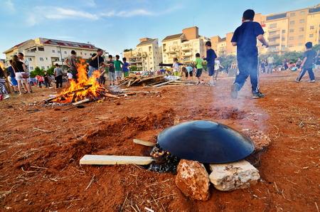 secular: TEL AVIV, ISRAEL - MAY 18, 2014: Secular Israeli Kids having fun at Lag BaOmer with taboon bread, bonfires and food Editorial