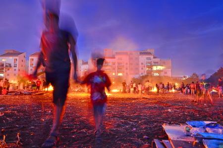 secular: TEL AVIV, ISRAEL - MAY 18, 2014: Secular Israeli Kids having fun at Lag BaOmer with bonfires and food - motion, long exposure