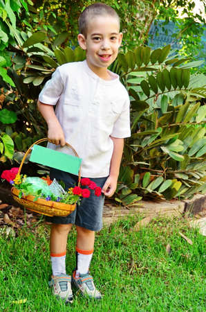 A young boy holding a colorful basket of fresh fruit (Bikkurim) decorated with flowers.  The basket is prepared traditionally to celebrate the Jewish festival of Shavuot (Feast of Weeks) or Pentecost. photo