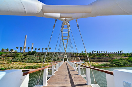 The Bridge of Strings in Hadera Stream Water Park with the Orot Rabin (formerly Maor David) power plant in Hadera, Israel - super wide angle view Stock Photo