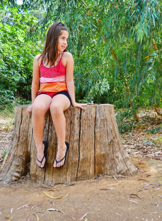 flops: Teenager girl sitting on a sawed giant eucalyptus tree trunk in summer dress