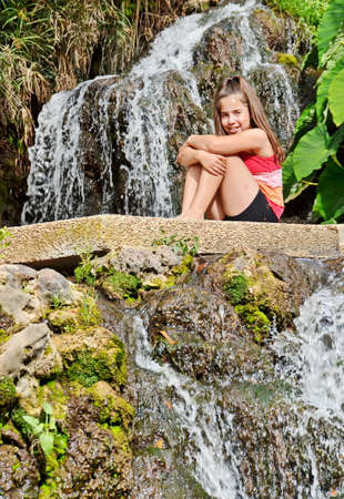 Teenager girl sitting in an oasis of waterfall, pond, and Elephant Ear plants in a kibbutz in Northern Israel.  Water is pumped from the nearby Jordan River. photo
