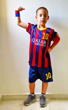 TEL AVIV, ISRAEL - JUNE 8, 2014: A boy standing proud in FC Barcelona Football  Soccer blue and red striped Uniform featuring #10 - Lionel Messi  and Qatar Airways banner