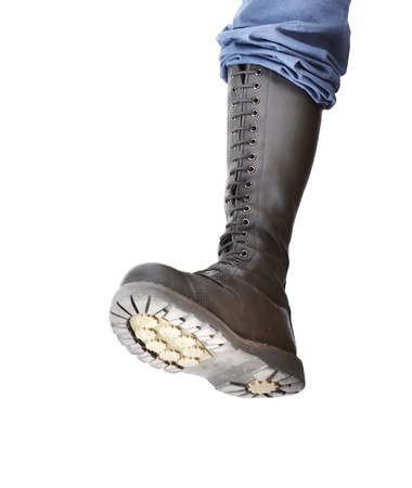 steel toe boots: A tall lace-up combat boot stomping with the sole visible