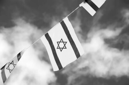 Israel flags in a chain in white and blue showing the Star of David hanging proudly for Israels Independence Day (Yom Haatzmaut) - black and white photo