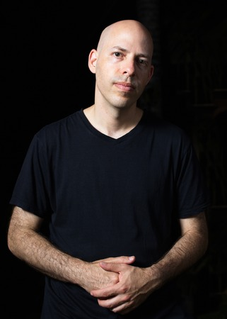 40 year old: Low-key portrait of a 40 year old bald man on black background with crossed hands Stock Photo