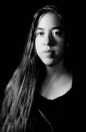 rembrandt: Dramatic low-key Rembrandt lighting portrait of an 18 year old young woman with long hair on black background in black and white (B&W) Stock Photo