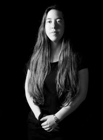 18 year old: Dramatic low-key Rembrandt lighting portrait of an 18 year old young woman with long hair on black background in black and white (B&W) Stock Photo