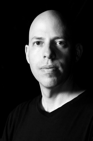 lowkey: Low-key black and white Rembrandt lighting portrait of a 40 year old bald man on black background Stock Photo