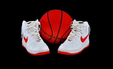 Pair of high-top classic Nike AF-1 Air Force 1 white leather basketball shoes sneakers with a basketball, isolated on black