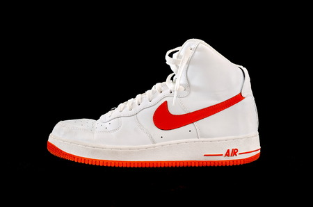 A high-top classic Nike AF-1 Air Force 1 white and orange leather basketball shoe sneaker, isolated on black