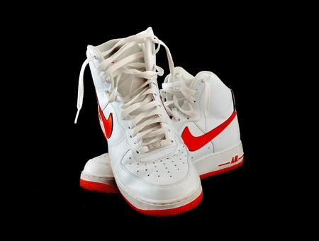 Pair of high-top classic Nike AF-1 Air Force 1 white leather basketball shoes sneakers, isolated on black