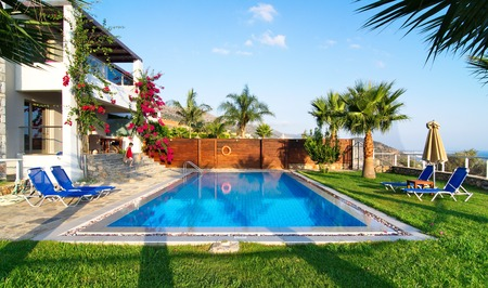 MALIA, GREECE - JULY 21, 2014: Villa with a private pool and garden on a summer vacation in golden hour light.  Malia, Crete near Hersonissos and Heraklion.