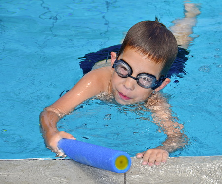A 6-year-old boy having fun in the swimming pool with a toy water squirt gun photo