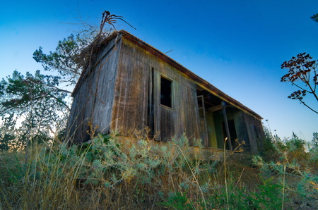 Creative Light painting of an abandoned wooden cabin in rural Israel with blue hour sky - wide angle view photo