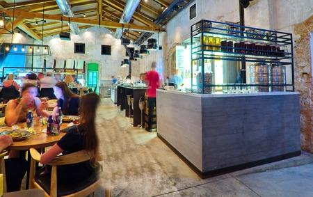 TEL AVIV, AUGUST 15, 2014  Patrons enjoying dinner in a modern open kitchen restaurant in Tel Aviv.   The restaurant is part of the hip Sarona district featuring restored Templer buildings