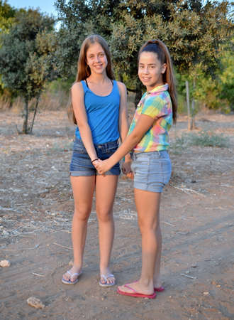 12 year old: Best Friends Forever - two 12 year old teenage girls  holding hands at sunset