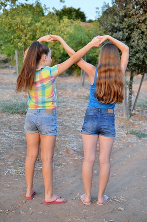 12 year old: Best Friends Forever - two 12 year old teenage girls  holding hands in an infinity forever sign to signify BFF Stock Photo