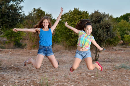 12 year old: Best Friends Forever - two 12 year old teenage girls  jumping frozen in mid air