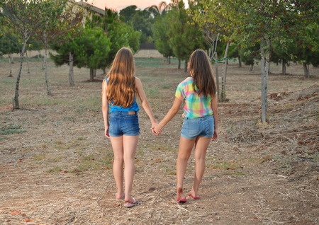 Best Friends Forever - two 12 year old teenage girls  holding hands at sunset photo