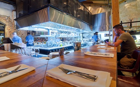 TEL AVIV, AUGUST 15, 2014: Chefs cooking dinner in a modern open kitchen restaurant in Israel with a patron sitting at the bar.  Part of the hip Sarona district featuring restored Templer buildings.